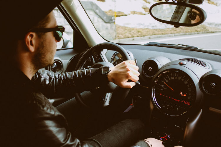 Young man driving a car Car Car Interior Dashboard Day Driving Human Hand Land Vehicle Leisure Activity Lifestyles Mode Of Transport One Person Outdoors Real People Sitting Speedometer Steering Wheel Transportation Young Adult
