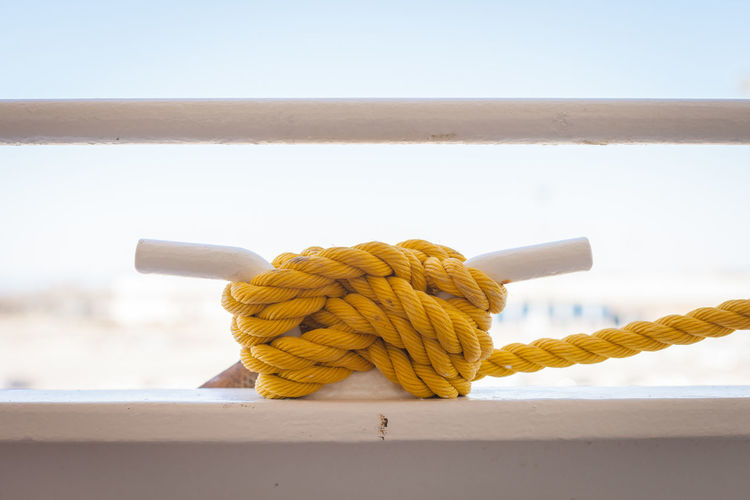 Close-up of yellow rope on railing