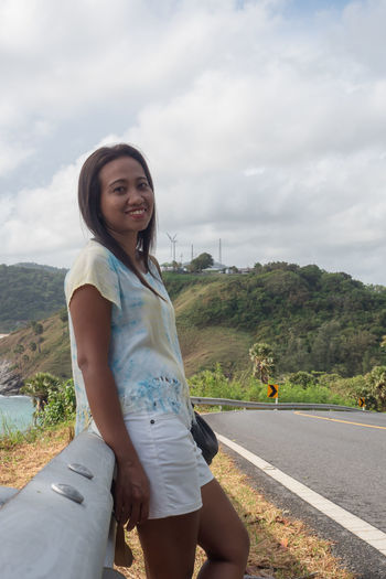 Portrait of smiling young woman standing on road against sky