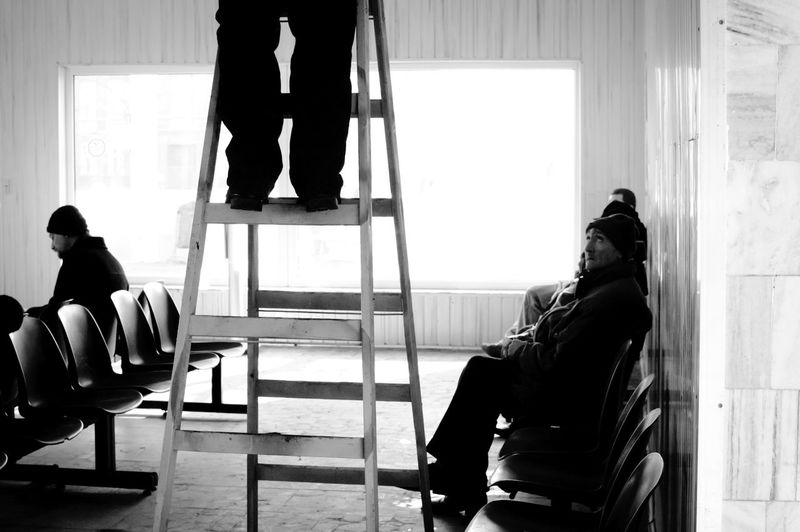 Low section of man on ladder by people sitting in waiting room