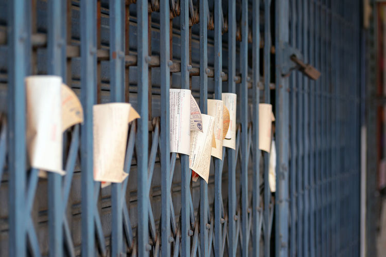 Close-up of paper hanging on metal gate