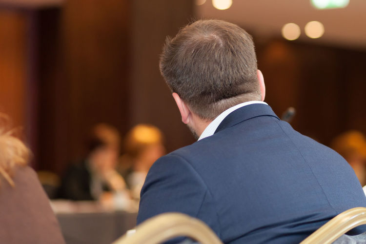 Rear view of businessman sitting on chair in conference
