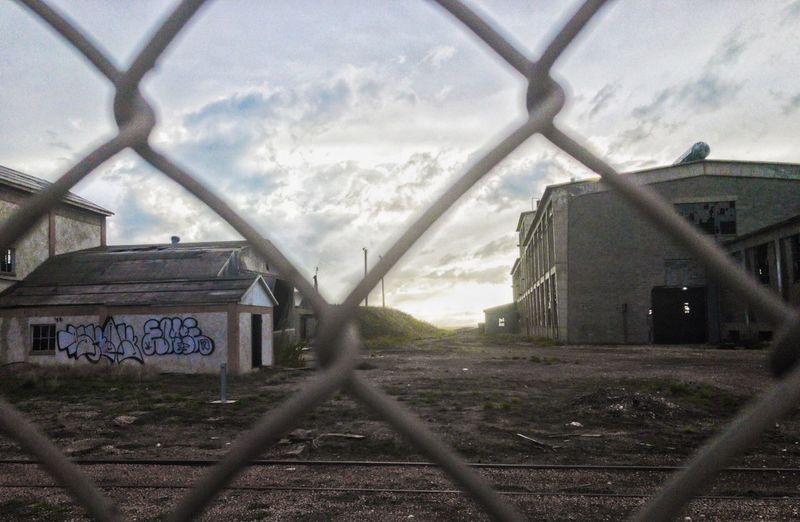 Railroad tracks amidst field against sky seen through chainlink fence