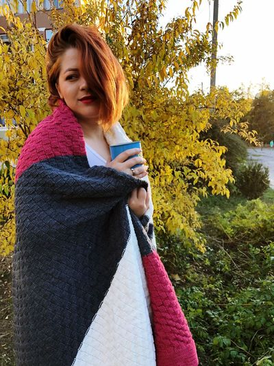 Thoughtful young woman wrapped in blanket while having drink against plants