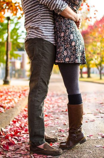 Low Section Of Couple Embracing On Footpath During Autumn