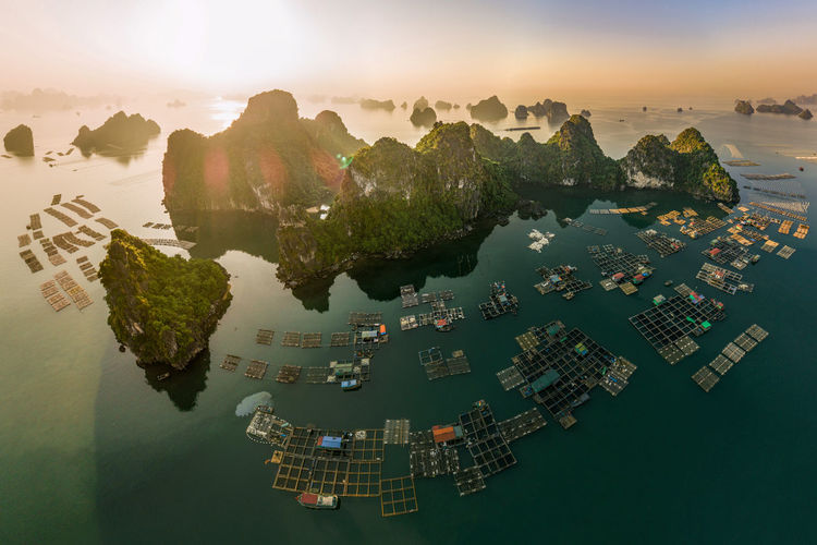 Aerial view of built structure in sea during sunset