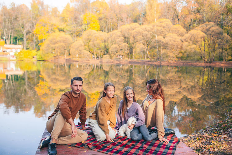 Group of people sitting by autumn trees