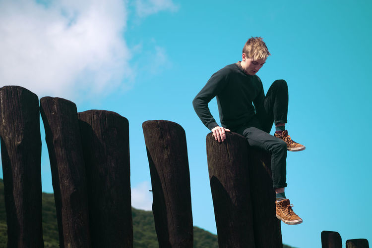 Low angle view of young man sitting on wood against sky