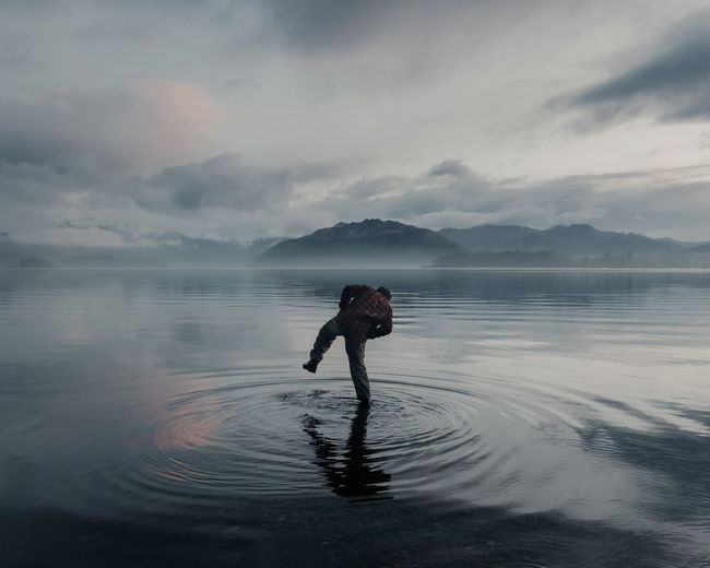 Rear view of man standing in lake against cloudy sky