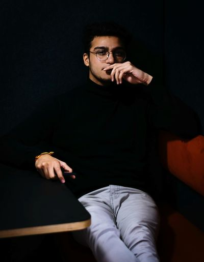 Portrait of confident young man in eyeglasses sitting in dark