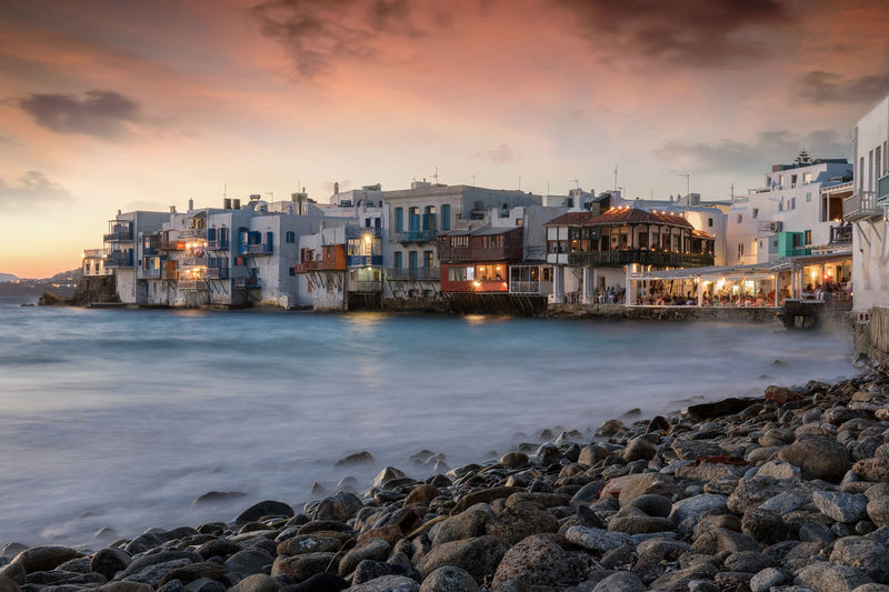 Sunset over the town of Mykonos island in Greece Greek Lights Tourist Attraction  Travel Architecture Bay Beach Cloud - Sky Cyclades Dusk Evening Greece Illuminated Island Little Venice Motion Mykonos Pebble Sea Sky Sunset Tourism Town Travel Destinations Water