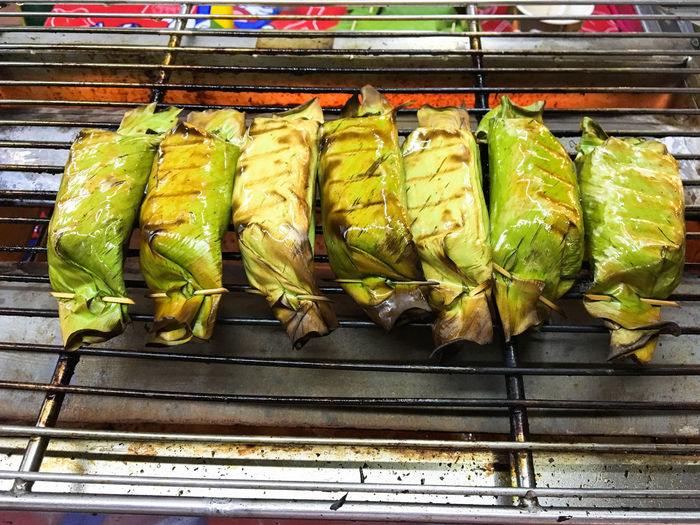 High angle view of food wrapped in leaves on barbecue