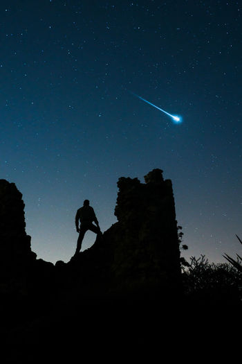 Man standing on ruins on starry sky with falling star