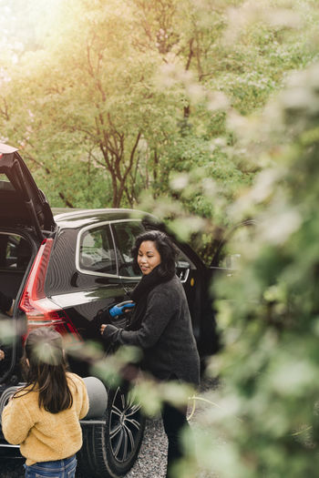 Young woman sitting by car on tree
