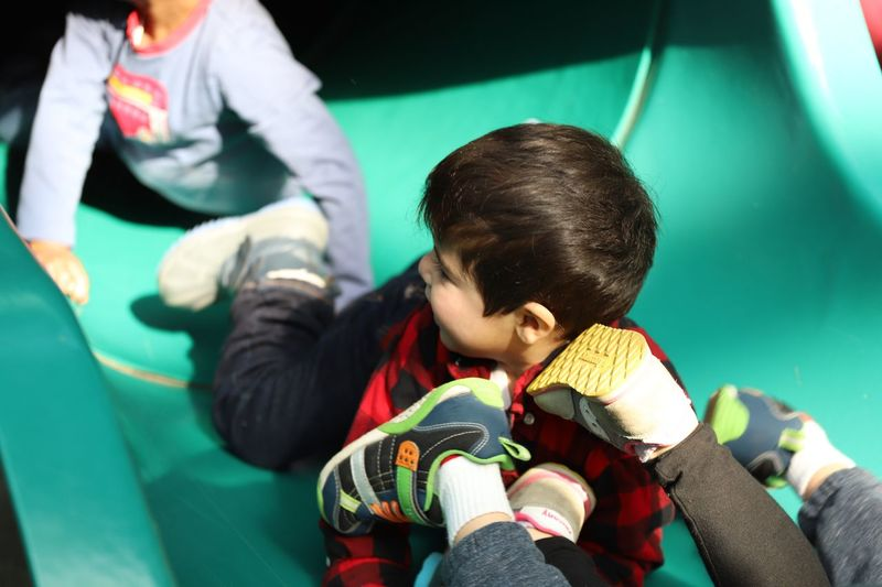 High Angle View Of Siblings Sliding On Slide In Playground