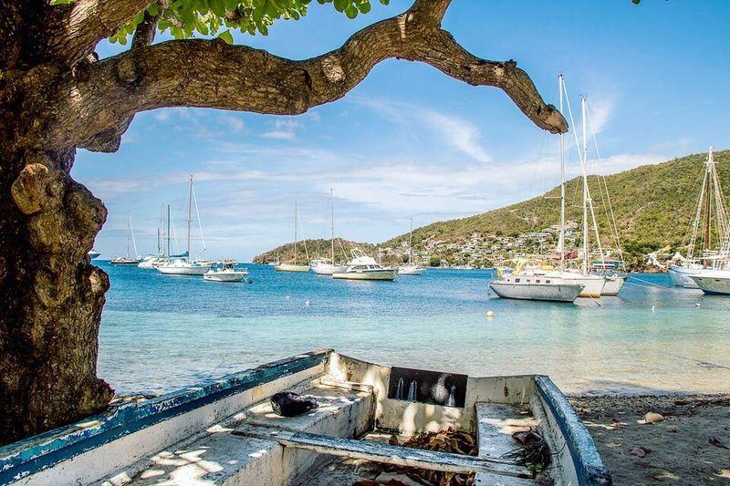 Sailboats moored on sea against blue sky