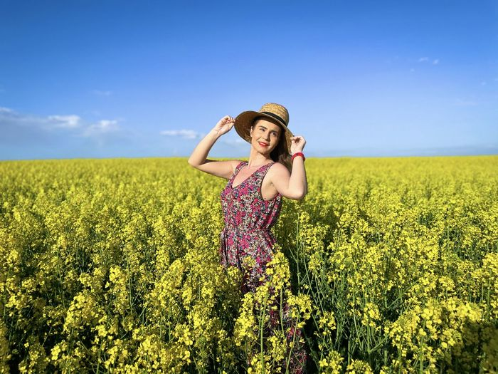 Happy woman wearing dress and hat in a field of canola flowers on a sunny day