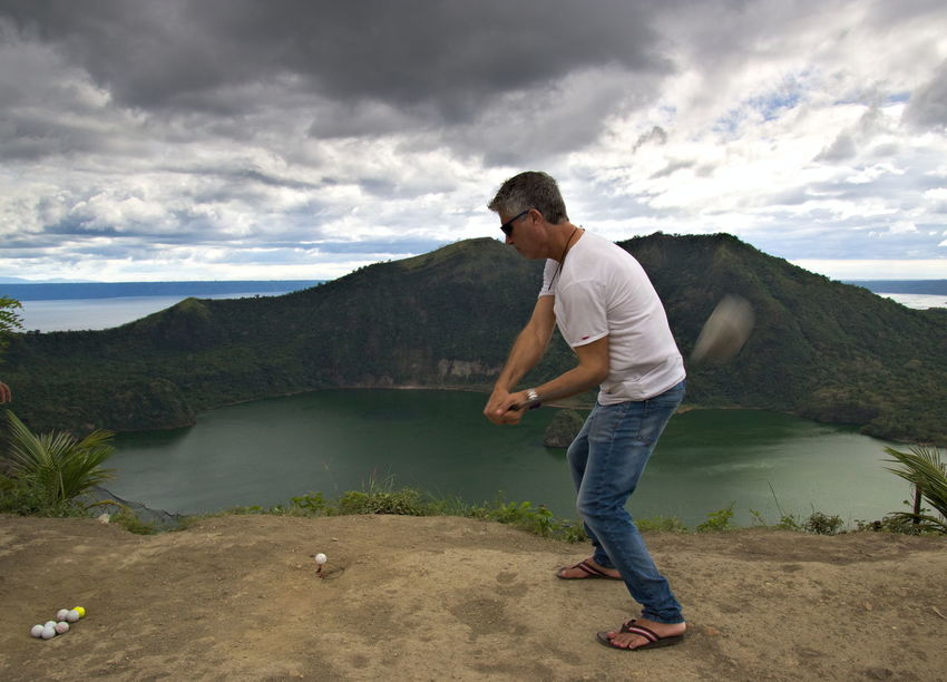 Tourist playing golf on Taal volcano Adult Cloud - Sky Drive Golf Leisure Activity Nature One Man Only One Person Outdoors People Tourist Vacations Connected By Travel