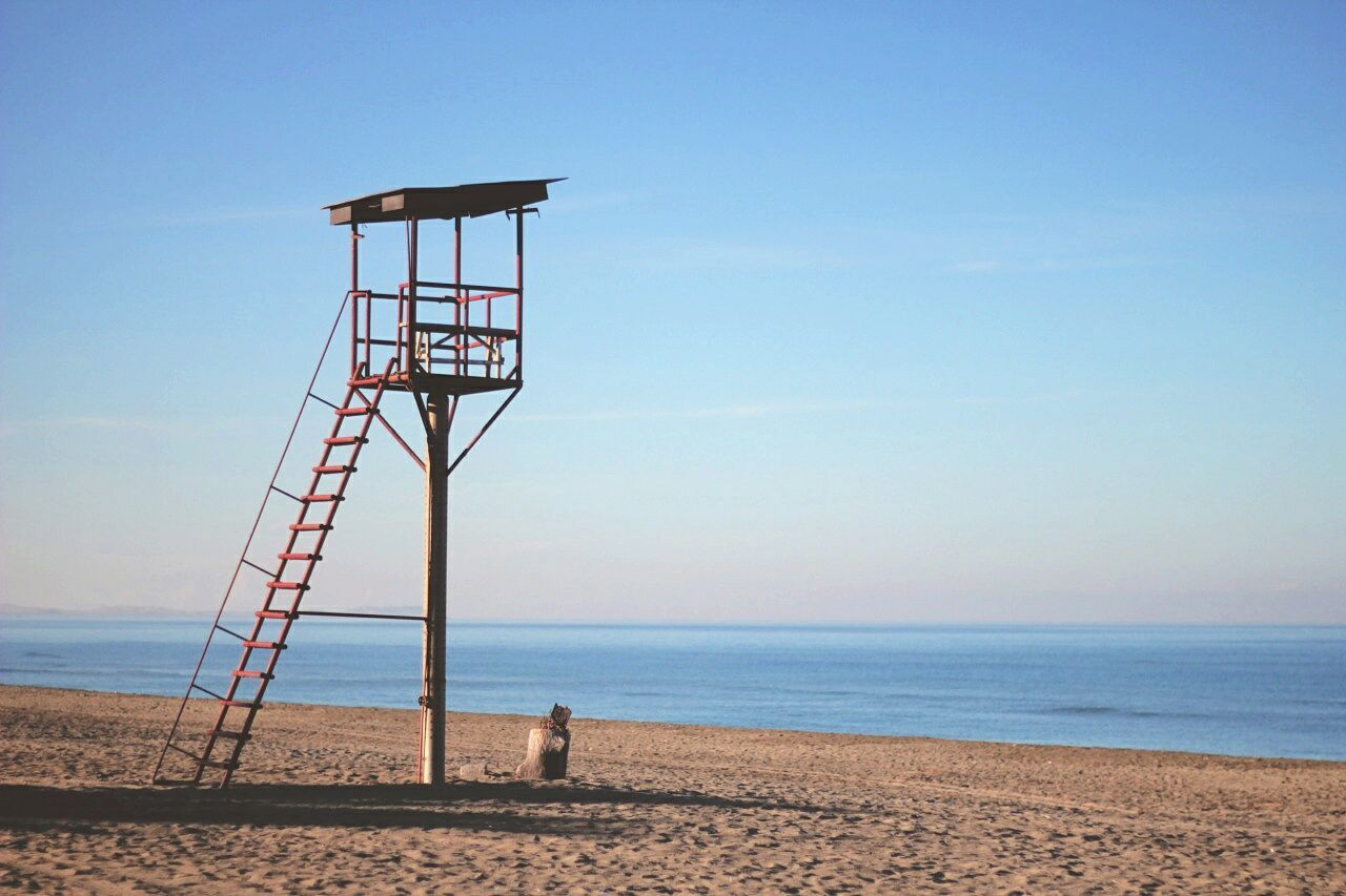 sea, beach, horizon over water, tranquil scene, tranquility, sand, day, lookout tower, outdoors, scenics, built structure, water, lifeguard hut, beauty in nature, nature, no people, architecture, clear sky, blue, sky