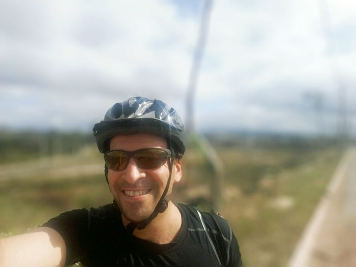 Portrait of happy cyclist standing on field against sky