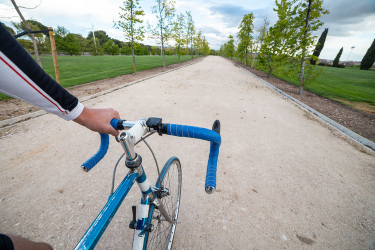 Man riding bicycle on road amidst field