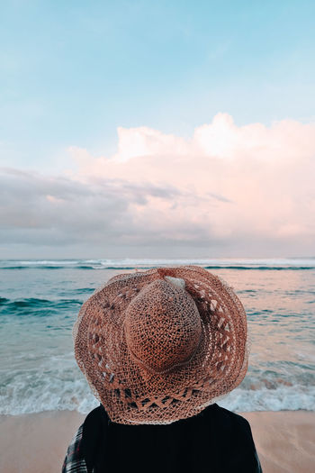 Man wearing hat at beach against sky
