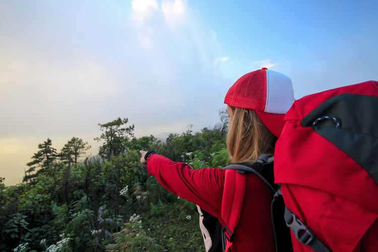 The women wearing red shirts are watching the view. Adult Beauty In Nature Clothing Day Hairstyle Hat Leisure Activity Lifestyles Nature One Person Outdoors Plant Real People Red Sky Tree Waist Up Warm Clothing Winter Women Young Adult