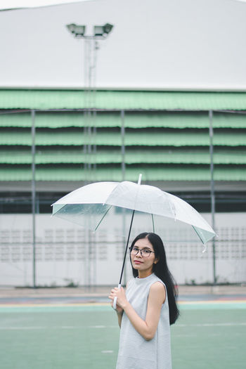 Portrait of smiling young woman holding umbrella standing on footpath against building