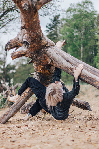 Full length of woman climbing on tree trunk in forest