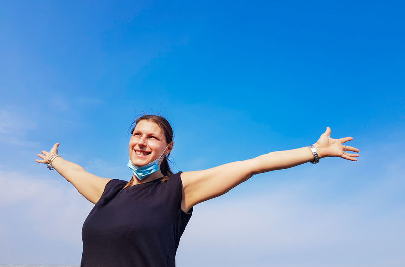 Happy woman with arms outstretched standing against blue sky