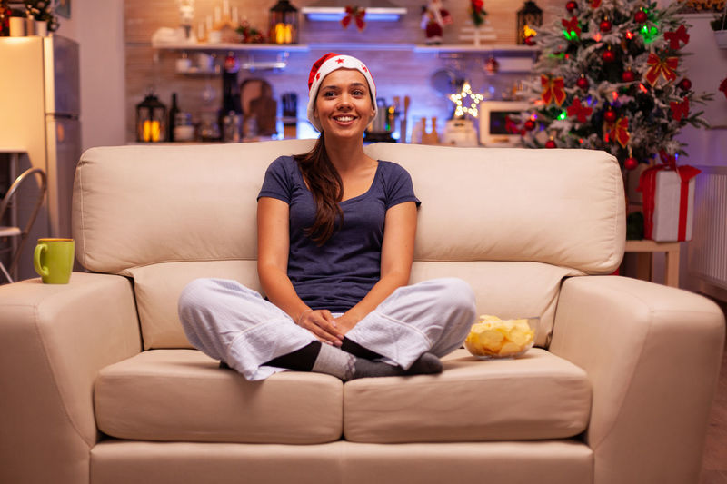 Portrait of smiling young woman sitting on sofa at home