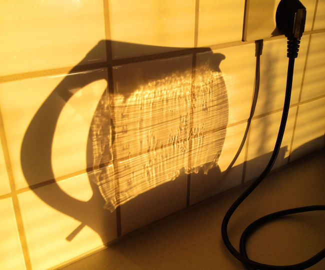 Shadow of container on wall with electric socket