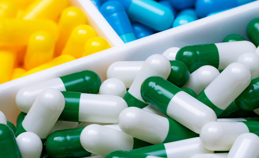 Selective focus on green-white capsule pills in plastic box on blue and yellow capsule pills.