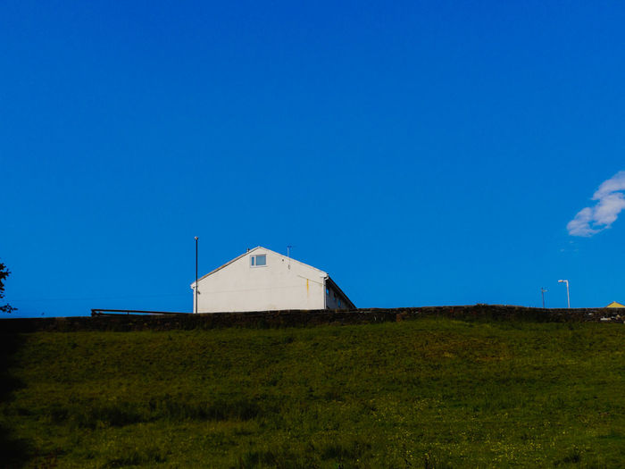 Barn on field against clear blue sky