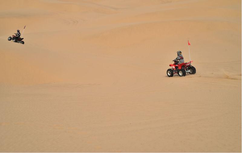 People Riding Quadbikes On Desert