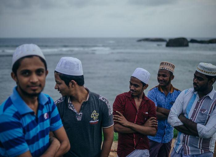 Men standing in sea against sky