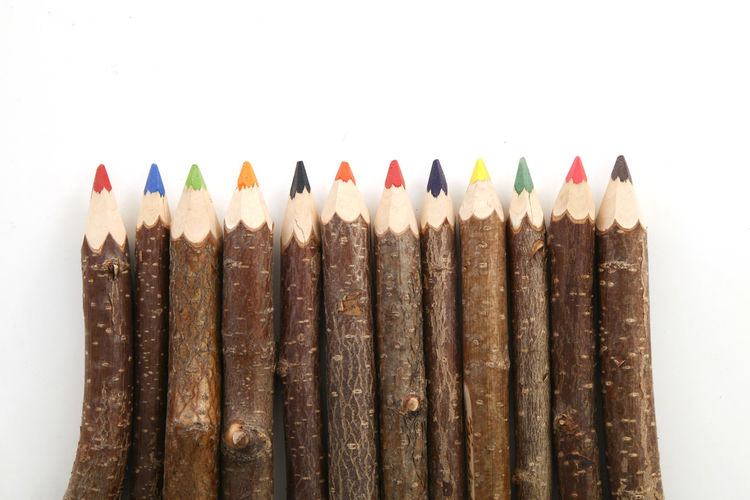 Close-up of multi colored pencils against white background