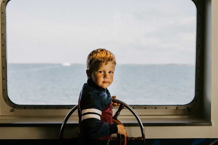 Portrait of boy in sea against sky