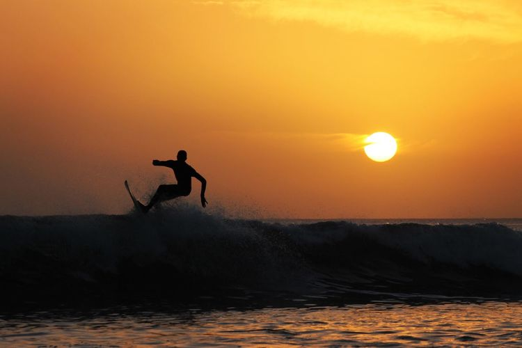 Sea Sunset Water Real People Leisure Activity Motion Lifestyles Beauty In Nature Nature Wave One Person Surfing Men Surfboard Excitement Sky Sport Fun Jumping Outdoors