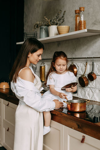 Month and daughter preparing food at kitchen counter