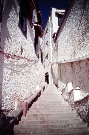 Low angle view of staircase amidst buildings