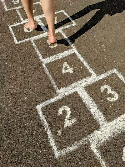 Low section of boy playing hopscotch