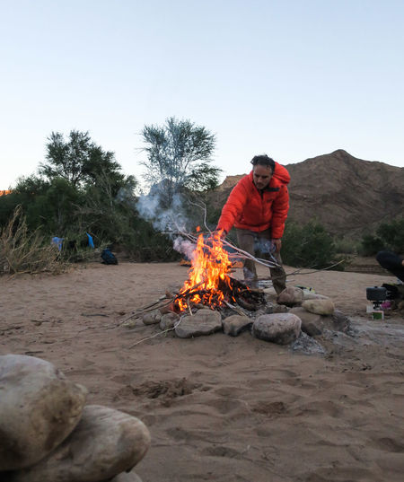 Male hiker adding wood to burning campfire Adventure Bonfire Burning Campfire Fire Flame Fuel Let's Go. Together. Man Men Namibia Nature One Man Only One Person Orange Color Outdoor Photography Outdoors Rock - Object Sand Tree Wilderness Wood - Material Young Adult