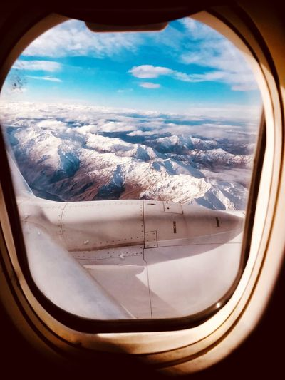 Scenic view of mountains seen through airplane window