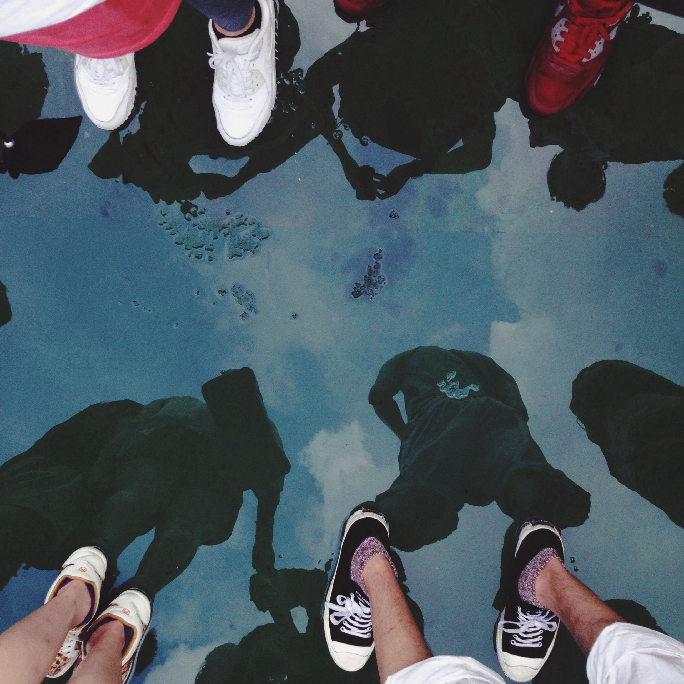 low section, person, lifestyles, shoe, personal perspective, leisure activity, human foot, men, standing, high angle view, togetherness, water, directly above, part of, unrecognizable person