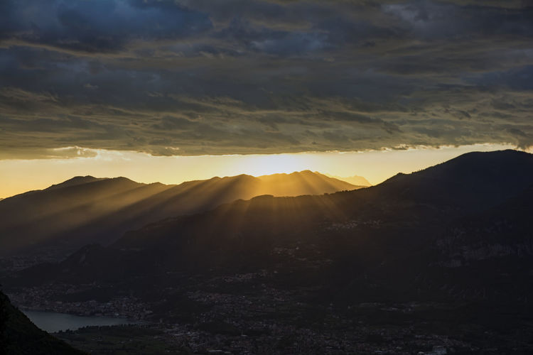 Storm clouds over silhouette mountains during sunset