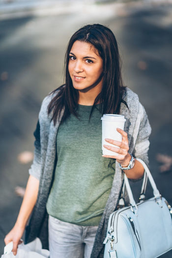 Girl With A Take-Away Coffee In The City Looking Stores And Shopping 20-29 Years 20s Autumn Beautiful City Coffee Dark Hair Lifestyle Shopping Vertical Composition Woman Young Cute Drink Holding Long Hair Looking One Person Outdoors Smiling Springtime Take Away Coffee Teenager Young Adult