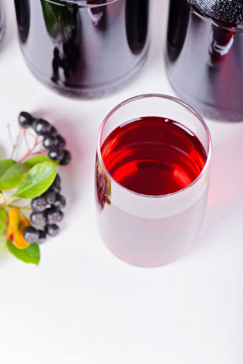 Syrup made from aronia berries, glass and bottles Aronia Alcohol Aronia Berries Aroniaberries Close-up Day Drink Drinking Glass Food Food And Drink Fragility Freshness Healthy Eating High Angle View Indoors  Liquid No People Red Red Wine Refreshment White Background Wine Wineglass