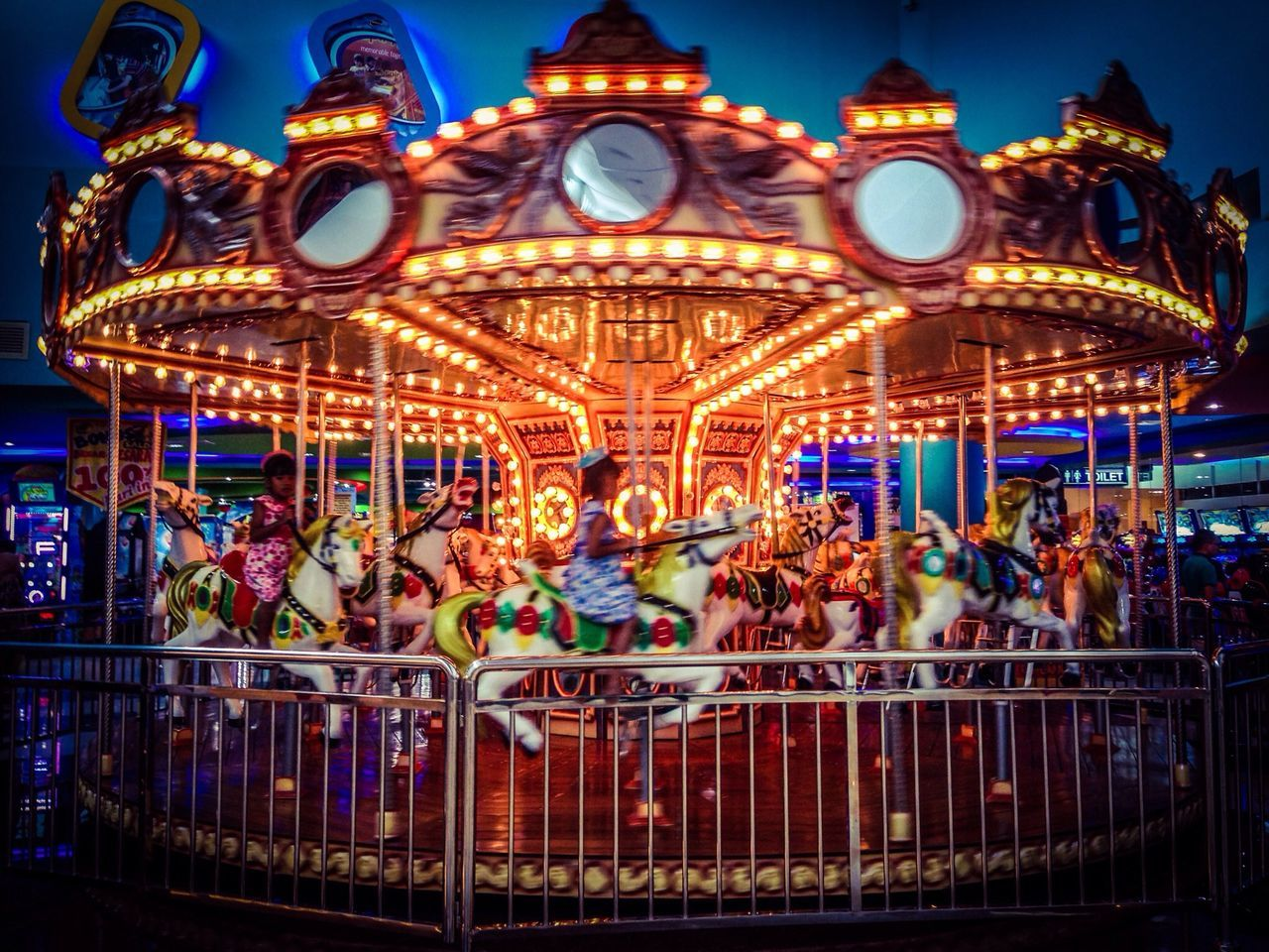 amusement park, carousel, arts culture and entertainment, amusement park ride, illuminated, leisure activity, merry-go-round, night, enjoyment, carousel horses, fun, outdoors, group of people, sky, people
