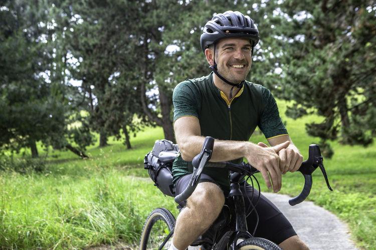 Man wearing helmet sitting on bicycle at park
